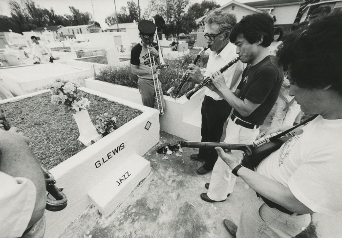 Reedmen Tom Sharpsteen & Ryoichi Kawai; banjoist Junichi Kawai and others pay homage at clarinetist George Lewis' grave, New Orleans. Photograph by William Carter, 1984
