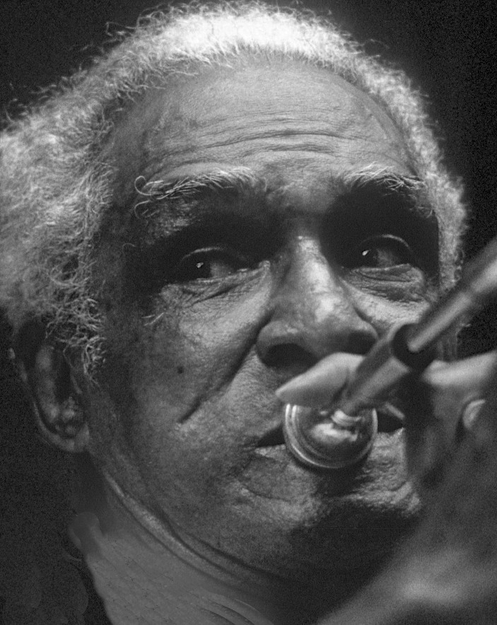 Trombonist Louis Nelson at a private party in the French Quarter. For many years Nelson was featured in the bands of Barry Martyn and others on countless European tours, as well as with trumpeter Kid Thomas and others across the U.S. under the Preservation Hall banner. The watchword of such brass players was a simple, honest sound derived from decades of experience processioning through the streets of the city by day and working down-home dance halls by night. Photograph by William Carter, 1984